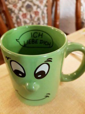 Die Kaffeetasse mit dem Gesicht lächelt den Rechtshänder an, dem Linkshänder würde sie den Tassenrücken zukehren.