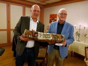 Hinrich Bangemann nimmt von Johan Doff, dem Präsidenten des Rotary Clubs Bathmen de Schipbeek, ein Brot als Begrüßungsgeschenk entgegen.