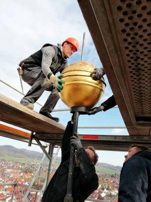 Die vergoldete Kugel wird von Mitarbeitern der Werkstätten für Denkmalpflege Quedlinburg abgenommen.