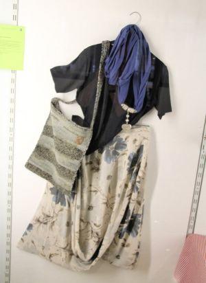 Kleidung wie Tasche sind handgeschneidert worden.