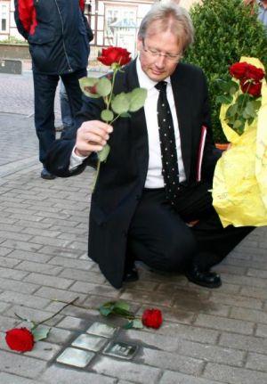 Dr. Gans legt rote Rosen um die Steine