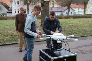Alexander Helbing und Valentin Möller von exabotix bereiten die Drohne vor, Frank Seela schaut genau zu