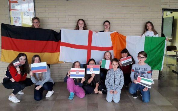 Die Projektteilnehmer halten Flaggen der verschiedenen Länder hoch, welche thematisiert wurden.