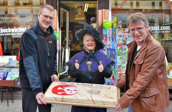 Mordharz-Team mit mörderischer Torte: Christoph Lampert (links) und Roland Lange schenkten Festival-Kollegin Susanne Kinne eine Torte zum Jubiläum ihrer Buchhandlung.