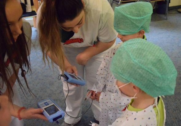 Puls messen: Gemeinsam prüften die Auszubildenden und die Kindergartenkinder, wie sich der Puls durch Bewegung verändert. (Foto: Helios Kliniken)