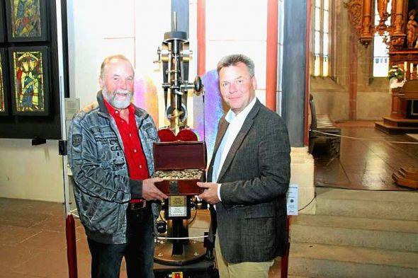 Detlef Hänsel (links) übergibt Pfarrer Beims 1.000 Euro.