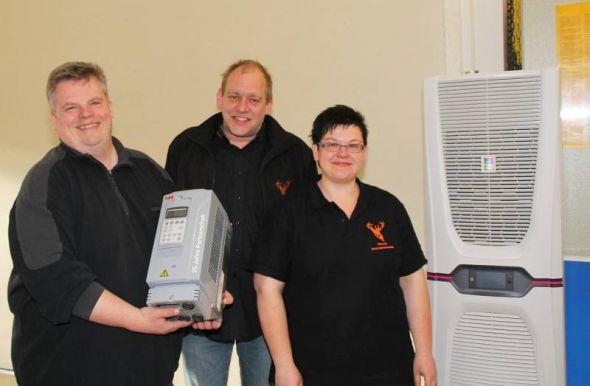 """Das Führungs-Trio (von links): Marcus Warlich, Ralf Mosebach und Chantal Lienauer-Warlich. Dabei ein großes Kühlaggregat für große Schaltanlagen und ein kleiner Frequenzumwandler, """"eine Art Gaspedal für Elektromotoren"""", so Warlich."""