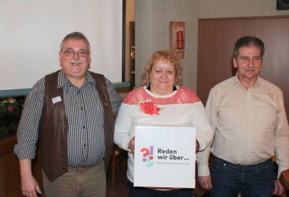 Foto: Der Ortsverbands-Vorsitzende (links) Klaus-Richard Behling, Schriftführerin Yvonne Willig (mit dem Motto) und der Referent Lothar Hanisch.