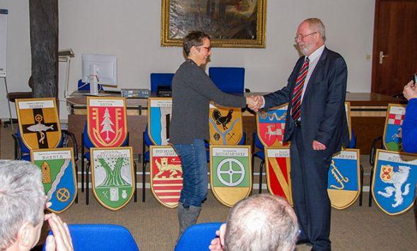 Amtsgerichtsdirektor a.D. Rolf Lutze übergibt per Handschlag die 14 Wappentafeln an Richterin Susanne Lojewski, die stellvertretende Amtsgerichtsdirektorin in Herzberg.