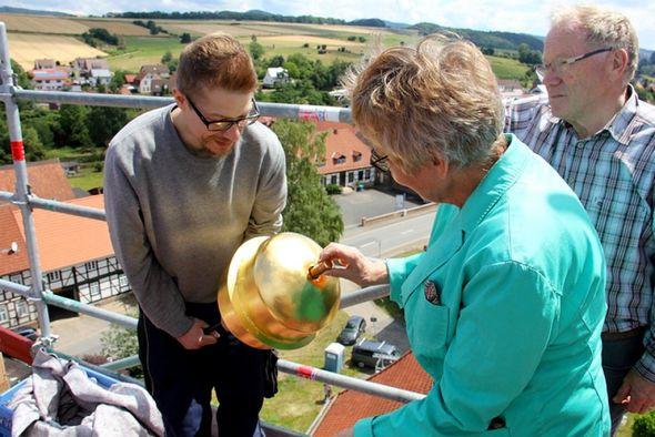 Gerlind Gottschling vom Kirchenvorstand lässt unter den Augen des Vorstandskollegen Friedrich Deppe (rechts) eine Zeitkapsel in die Kugel...