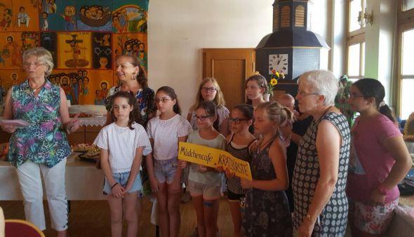 Markttreffleiterin Lilli Gans übergibt einen wohl gefüllten Umschlag an die Mädchen